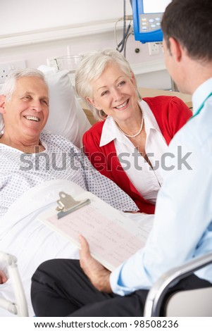 Doctor talking to senior couple on UK Hospital ward