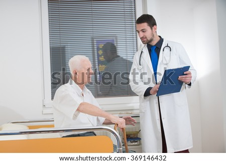 doctor talking to senior man in surgery