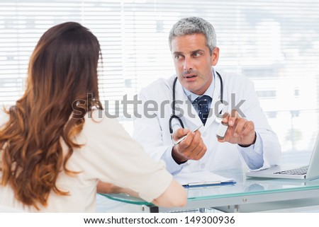 Doctor talking with his patient seriously in medical office - stock photo