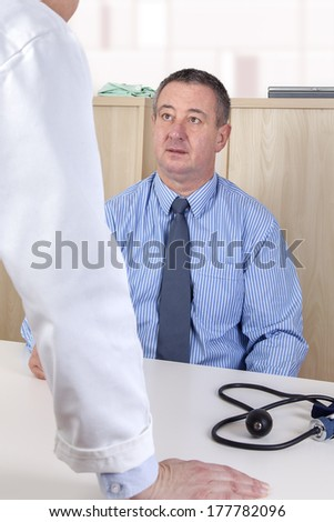 Doctor talking with man in the hospital management