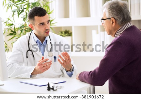 Doctor talking with old patient - stock photo