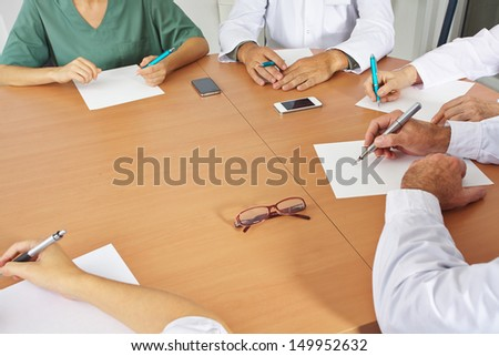 Doctor team in a meeting with pen and paper - stock photo