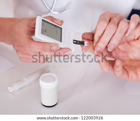 Doctor testing a patients glucose level after pricking his finger to draw a drop of blood and then using a digital glucometer - stock photo