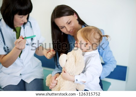 Doctor trying to exam baby's throat - stock photo