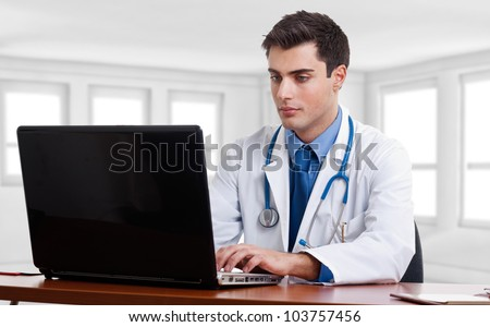 Doctor using a laptop computer on his desk - stock photo