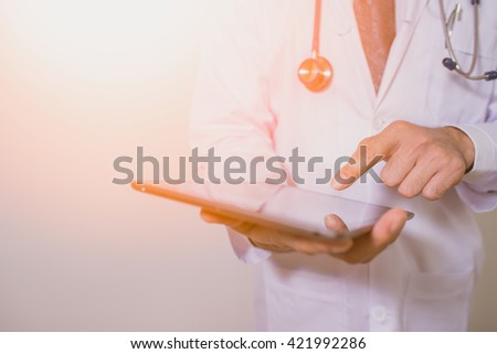 doctor using computer plane-table. man doctor. doctor concept vivid tone. Doctors have a duty to treat patients. Doctors wear white. Doctors working in hospitals. doctor  holding tablet. - stock photo