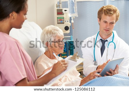 Doctor Using Digital Tablet In Consultation With Senior Female Patient In Bed - stock photo