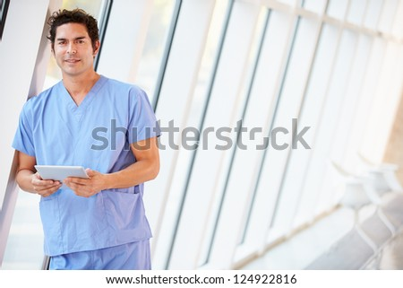 Doctor Using Digital Tablet In Corridor Of Modern Hospital - stock photo
