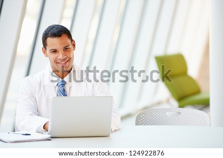 Doctor Using Laptop Sitting At Desk In Modern Hospital - stock photo