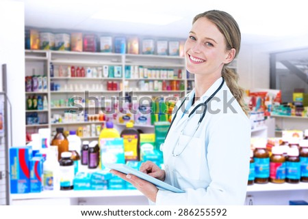 Doctor using tablet pc against close up of shelves of drugs