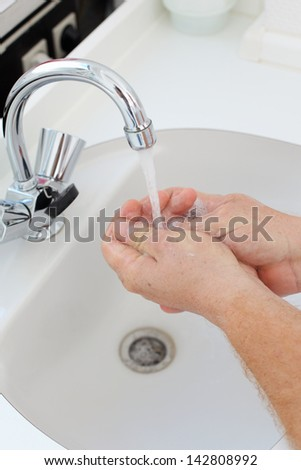 doctor washing hands in white basin in clinic - stock photo