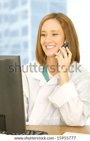 doctor wearing white coat analyse computer screen and on the phone. smiling with happy expression