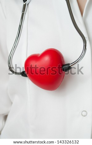 Doctor with a red heart and stethoscope - stock photo
