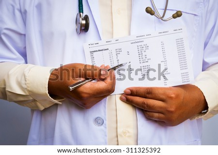 doctor with a stethoscope showing abnormal lab result - stock photo