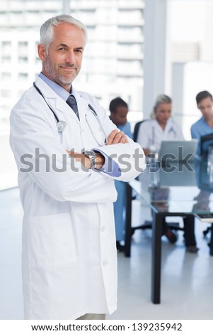 Doctor with arms crossed standing in front of medical team - stock photo