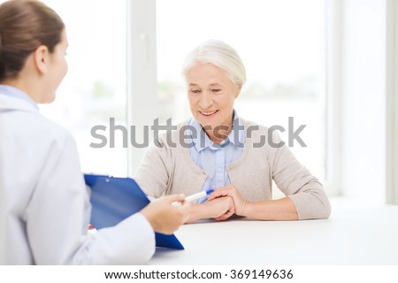 doctor with clipboard and senior woman at hospital - stock photo