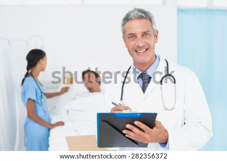 Doctor with colleagues and patient behind in the hospital - stock photo