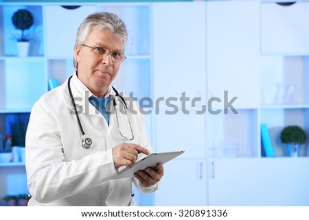 Doctor with digital tablet at his workplace
