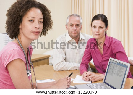 Doctor with laptop and couple in doctor's office - stock photo