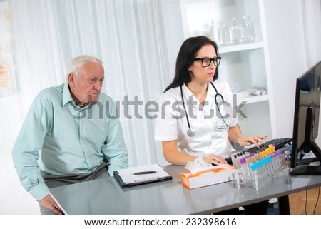 Doctor with male senior patient at office - stock photo