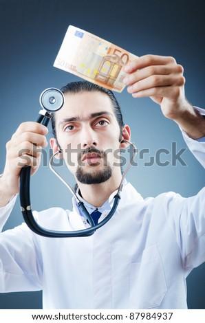 Doctor with money in studio - stock photo