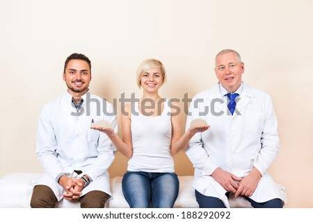 doctor with patient, young girl show breast implant, plastic surgery clinic - stock photo