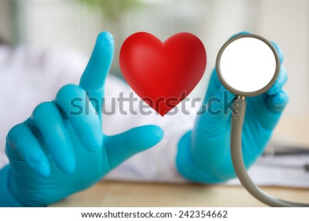 Doctor with stethoscope and red heart  in hand - stock photo