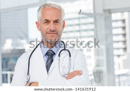 Doctor with stethoscope around his neck looking at the camera - stock photo