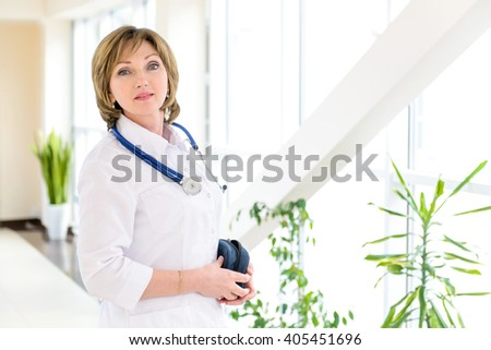 Doctor with stethoscope around his neck looking at the camera. Experience and Professionalism. - stock photo
