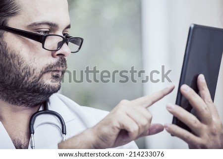 Doctor with stethoscope around his neck looking at the tablet PC - stock photo