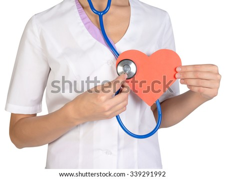 Doctor with stethoscope examines red paper heart.