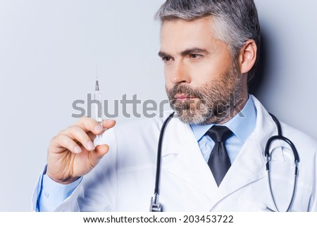 Doctor with syringe. Confident mature doctor holding syringe and looking at it while standing against grey background - stock photo