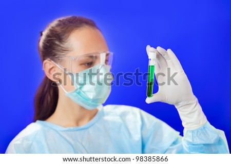 Doctor (woman) analyzing medical test tubes on blue background - stock photo