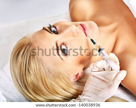 Doctor woman giving facial injections. Isolated. - stock photo
