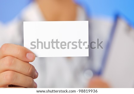 Doctor (woman) holding blank business card with copy space on blue - stock photo