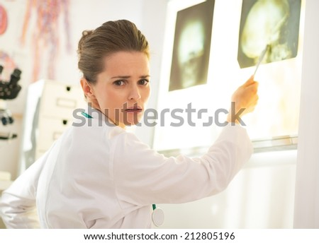 Doctor woman pointing on lightbox - stock photo