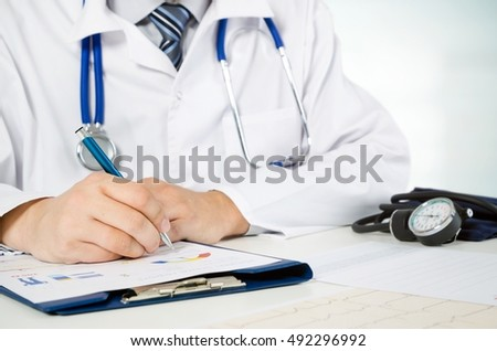 Doctor working at his desk in the hospital. Health care and medical concept.