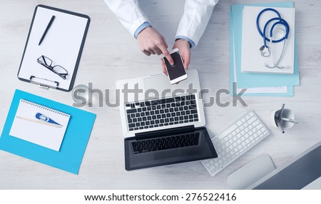 Doctor working at office desk and using a mobile touch screen phone, computer and medical equipment all around, top view - stock photo