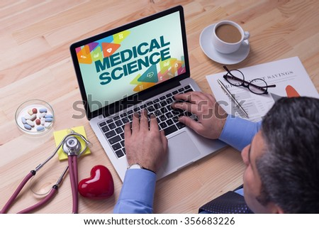 Doctor working on a laptop and MEDICAL SCIENCE on his screen - stock photo