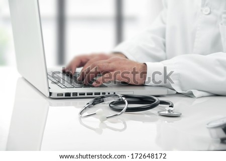 Doctor working on his notebook  - stock photo