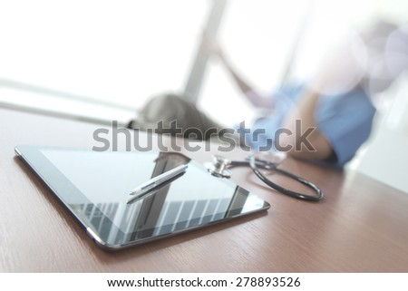 Doctor working with digital tablet in medical workspace office as concept  with overcast exposure - stock photo