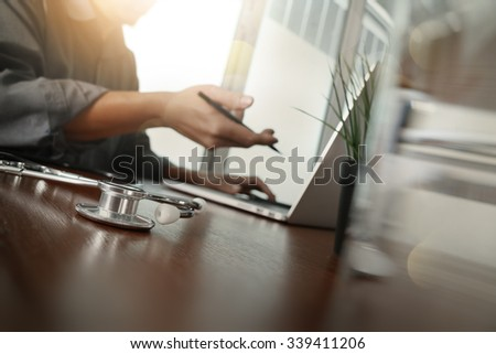 doctor working with laptop computer in medical workspace office and medical network media diagram with glass of water and green plant foreground as concept - stock photo