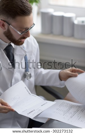Doctor working with test results of his patient at office - stock photo