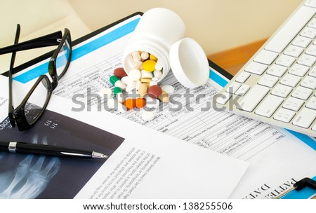 Doctor workplace. Pills, tablets, pen on patient history database - stock photo