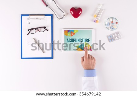 Doctor workplace with ACUPUNCTURE on tablet screen - stock photo