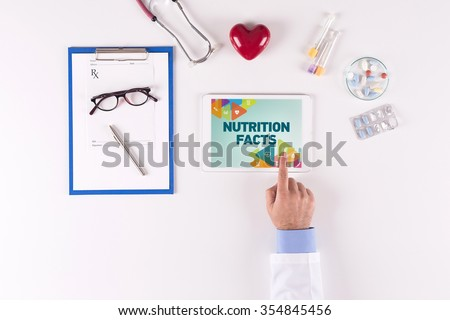 Doctor workplace with NUTRITION FACTS on tablet screen - stock photo