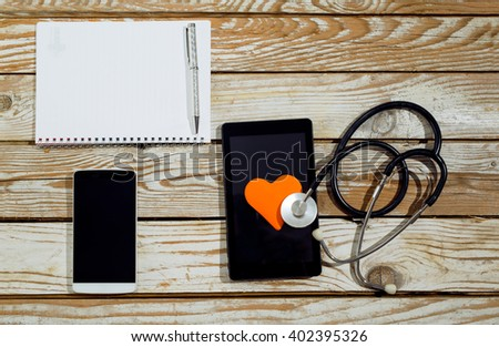 Doctor workplace with tablet and stethoscope on the sing of the heart,  on wooden background - stock photo