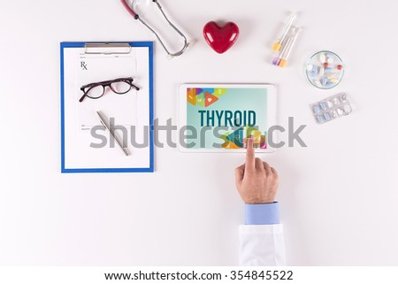 Doctor workplace with THYROID on tablet screen - stock photo