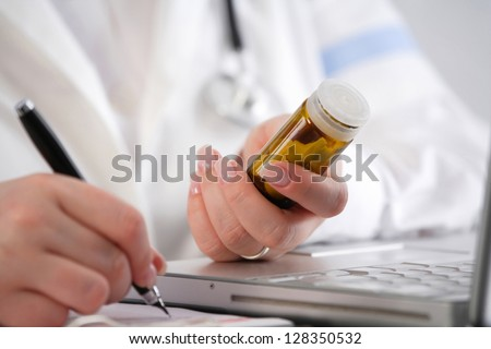 Doctor writing a prescription - stock photo