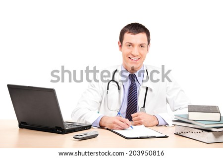 Doctor writing on a clipboard seated at his desk isolated on white background